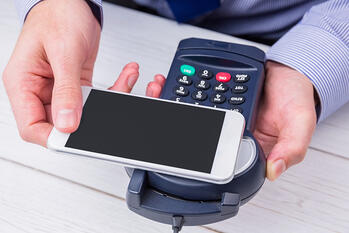 Man using smartphone to express pay on a wooden table