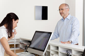 Mature male patient looking at female receptionist using landline phone and computer at reception in dentists clinic-1