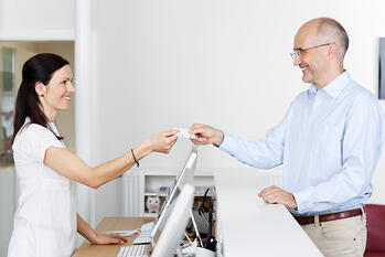 Mid adult female receptionist receiving card from patient in dentist clinic-1